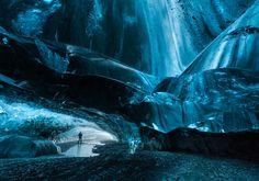 Landscape photo of a man standing in a blue glacier cave - Breidamerkur Glacier, South Iceland