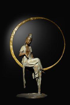 """子問老師作品- 作品名稱:33觀音-映慈 實際尺寸:L35xH53(cm) 創作理念: 因其法相為坐姿於水面月輪之上,遙望眼下水面的月光倒影,猶如水中觀月,月代表著沉靜、柔和之美,「心之淨化、水難守護」。 造型:觀音被月輪之光圈包圍的圓滿充盈,衣襟落於平靜水面之上泛起了漣漪,如一面明鏡,望之讓人觀心自照、心靜如水一般,呈現出作品柔順平和、慈善之美的延續,故名""""映慈""""。 Nirvana Buddhism, Japanese Buddhism, Asian Sculptures, Mahayana Buddhism, Spirited Art, Buddha Art, Japan Art, Sacred Art, Sculpture Art"""