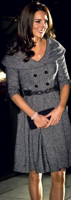 Kate Middleton in a Jesiré dress. The double breasted coat dress has an exaggerated shawl collar, three-quarter sleeves and a full skirt style. She completes the look with an Asprey Button Pendant.