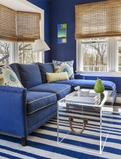 Blue and White living room, striped rug, blue sofa, natural shades      Digs Design Company