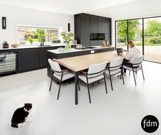 Deze strak, zwarte greeploos Fenix keuken is prachtig gecombineerd met een eiken houten geïntegreerde tafel.