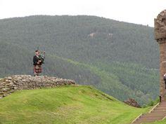 Un escocés ambientando con música de gaita el paisaje en el castillo.