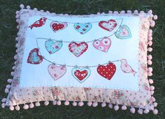 adorable string of hearts pillow in red, pink, and aqua from lovely little handmades