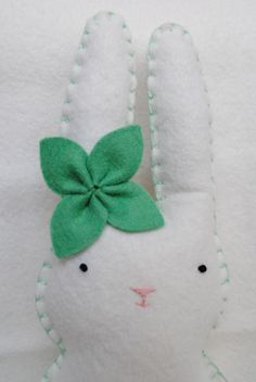 This sweet bunny is the perfect addition to any lucky girls room. She is 9 inches tall and is made of high quality white wool felt. Her sweet little face is all hand stitched. The stitching, her pocket (on the back) and her simple flower are all made of mint green colored felt and floss.  Her pocket is accented by a small white tooth.  Made of high quality wool felt and all hand sewn. Each piece is special and no two will ever be exactly alike. All my special tooth fairy pillows are made to…