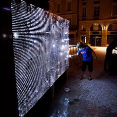 Water Light Graffiti by Antonin Forneau for DigitalArti Artlab.  Spraying a wall with water creates a graffiti with tiny points of light instead of paint