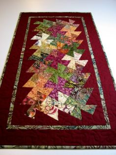 The rich colors of Autumns harvest give a striking bejeweled appearance to this quilted table runner measuring approximately 17.5 inches by 32.75 inches. Designed using twisted pinwheel blocks, the wines, golds, and greens appear to swirl together. A deep burgundy cotton solid serves as a border, and a coordinating batik appears as a narrow inner band and as the double fold binding. Layered with Warm and White cotton batting, and machine quilted with cotton thread in a meandering stitch edge…