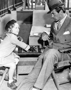 Shirley Temple and Gary Cooper play a father and daughter engaged in a game of draughts, in a scene from the film 'Now And Forever', directed by Henry Hathaway. 1934