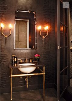 Powder Room by Shelley Gordon Interior Design. I love dramatic powder rooms.  The drama is created in this room with the contrasting textures and values of the shiny brass against the  dark chocolate crocodile wallpaper and stone.