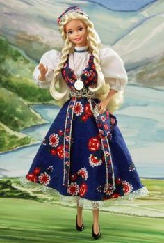 """1987 Icelandic Barbie® Doll   The Barbie Collection Mattel 03189  Special Edition Release Date: 1/1/1987 Most of Icelandic Barbie doll's ancestors were Vikings from Norway, and her costume reflects that influence. She wears a blue jumper dress known as a """"bunad. """" A light blue apron, trimmed with golden braiding, is tied around her waist. Her crisp, white blouse features beautiful pouffed sleeves. Icelandic Barbie doll wears long braids, very common in both Norway and Iceland, which are…"""