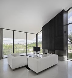 Modern Living Spaces // white interior with a statement fireplace at the Vidigal House by Contaminar Arquitectos