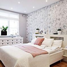 quarto de casal decorado com papel de parede floral cinza ebranco, móveis brancos