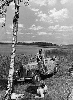 Ausflug mit dem Auto, 1937. Ein Paar macht mit dem Auto einen Ausflug. Die Frau liegt am Seeufer im Gras, der Mann sitzt in der Badehose auf seinem Auto der Marke Mercedes. Timeline Classics/Timeline Images #30er #1930er #Ausflug #Sommer #See #Oldtimer #Pause