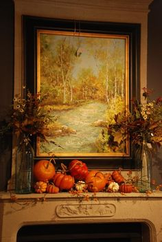 Lovely fall fireplace decor with gourds and leaves flanking landscape by Nell Hill's.