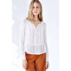 Alice & UO White Giovanna Top Light and sheer button placket blouse trimmed with fluttery dropped peplum hem by Alice Ritter's exclusive collab label, Alice & UO. Pleated accents at the front with long sleeves hemmed with button cuffs. Rayon, cotton. Machine wash. Urban Outfitters Tops Blouses