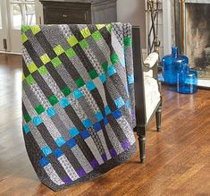 This throw appeals to modern and contemporary quilters, but traditional quilters can't resist the bold, bright colors. Black, gray, and white prints make the bright solids stand out in this simple, yet irresistible setting. Contemporary quilt patterns are the perfect way to make traditional quilt arrangements pop!
