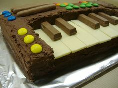 Keyboard cake. The black keys are Kit Kat pieces and the white keys are small Milkybars turned upside down so the smooth side is on top. The rest of the cake is just two rectangular chocolate sponge cakes. I cut a smaller rectangle out of one of the cakes to make space for the keys, sandwiched them together with chocolate buttercream, covered the whole thing with more buttercream and decorated it with MMs and chocolate fingers.