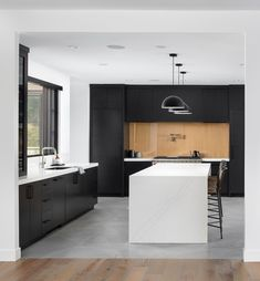 Crisp and clean contemporary black and white kitchen design to swoon over. Dramatic black modern cabinetry, white quartz waterfall kitchen island finished off with a white oak backsplash creating a charming contrast. #BlackAndWhiteKitchen #ContemporaryKitchen #KitchenIsland