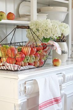 Elegant white stands out for this kitchen with the colourful apples around.