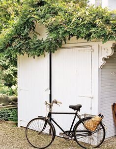 Wisteria drapes this little garden shed. A vintage corbel was added. This charming little white shed belongs to Children's-book illustrator James Halestill who  still rides the bicycle he owned as a boy! photo credit: Steven Randazzo. {I'd originally pinned this almost a year ago now!Wow! I am pinning again with provide proper credits. : )} #shed #garden
