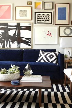 One With the Furniture Gallery Wall: This graphic art collection has a distinct feel of being thoughtfully collected over time. The bold black-and-white pieces match the pillow and rug, and pops of color add life to the room. Note how the art is grouped around the sofa and lamp.