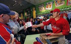 Philadelphia Phillies' Chase Utley gives out booklets to fans, as part of a fan appreciation event, during the Phillies' exhibition baseball game