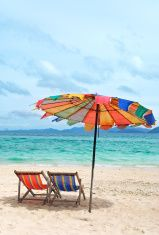 Beach chair and colorful umbrella on the beach stock photo