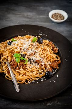 Pasta with tomato sauce, black olives, basil and pine nuts