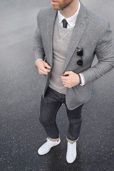 Try pairing a grey wool suit jacket with charcoal jeans for your nine-to-five. Opt for a pair of white leather low top sneakers for a more relaxed feel. Shop this look on Lookastic: https://lookastic.com/men/looks/blazer-crew-neck-sweater-dress-shirt/21040 — White Dress Shirt — Charcoal Tie — Grey Crew-neck Sweater — Black Sunglasses — Grey Wool Blazer — Charcoal Jeans — White Leather Low Top Sneakers