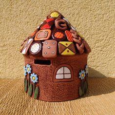 Pokladnička Točena na kruhu, následně ručně modelovaná. Peníze se vkládají otvorem pod střechou a vybírají dveřmi, kreré se dají odvázat a zase přivázat. Výška 18 cm, průměr 14 cm.