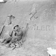 A Brit takes a smoke break between the fighting. *Note the propaganda on the wall.