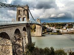 Wales, being a country in the United Kingdom has some very pleasant roads for a scenic drive. This is due to the fact that it is largely bordered by the Irish Sea to its North. Puzzle Of The Day, Irish Sea, Anglesey, Suspension Bridge, North Wales, Tower Bridge, Places To See, Countryside, Britain