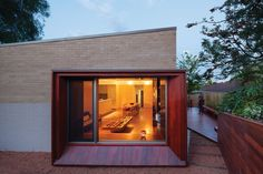 The extension's bay window frames a view out to the terraced garden, or back into  the warmly lit living space.