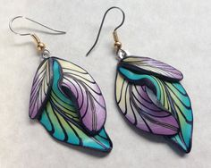 The earrings are handmade, one of a kind, lightweight and durable. I begin by mixing blocks of polymer clay to make gradients of color, then roll