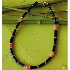 Onyx Necklace--Auspicious Beauty. This exotic Onyx Necklace has stunning symmetry. Interspersing its gorgeous triplets of onyx tube beads are perfect orbs of red aventurine. Gold-plated brass discs, beads and lobster clasp. Hand strung in the U.S.A.