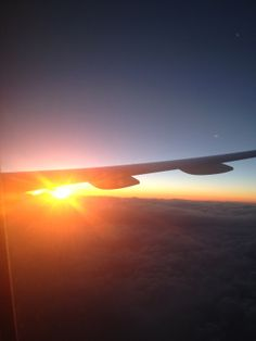 Photograph from a plane window of the sunrise over the clouds above the atlantic ocean.