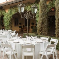 White folding chairs and white linens in the Piazza Toscana courtyard at this outdoor wedding reception | Gretchen Wakeman Photography | villasiena.cc