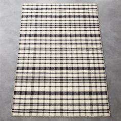 """checks, please. A mix of masculine and modern, this handloomed flatweave is tailor-made for the office, dining room—anywhere you want to step up the sophistication. Soft wool blend in an unstructured grid of black and soft ivory makes a statement without taking over.How will it look in your room? 12""""x12"""" rug samples are available in stores for a fee refundable upon return of the sample."""