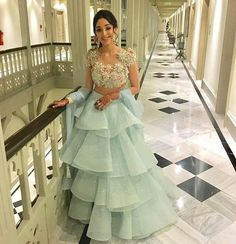 Indian wedding gowns - Setting our Hearts Aflutter! Roshini Kapoor is the epitome of Romance in an ice blue Ruffle lehenga and tutti frutti floral choli by Abu Jani Sandeep Khosla Couture abujanisandeepkhosla couture Indian Fashion Dresses, Indian Gowns Dresses, Indian Designer Outfits, Indian Wedding Gowns, Indian Bridal Outfits, Sangeet Outfit, Designer Party Wear Dresses, Designer Wear, Lehnga Dress