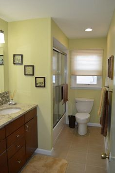 As you first walk into this newly remodeled bathroom you are eased by the soothing earthy effect it has on you. The warm browns of the vanity and accessories are invigorated by the vivd green on the wall and balanced by the neutral floor tile.
