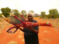 Paniny Mick (Amata Tjala Arts) holding her red Tjanpi Tjulpu (bird)