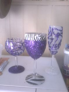 DIY wine glasses Use any glue that dries up clear,make your design and sprinkle on glitter.let dry for 30mins. Then use designed paper or more glitter for the bottom of the glasses..around the rim of the glass,use (colorful or design) tape.