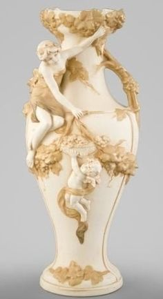 porc.Royal DUX___ Antique FigureCzechoslovakia ~ Royal Dux ~ Ivory and matte gold porcelain vase ~ Baluster form in the Art nouveau style ~ The shoulder with a seated deux-couleur- (draped nude) gilded spirit ~ Attended by a basket-bearing putto ~ Circa 1925-1950
