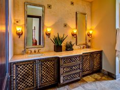 A relaxing, modern Mediterranean bathroom retreat has a double vanity bearing an intricate geometric pattern that echoes the square tilework of the backsplash and flooring.