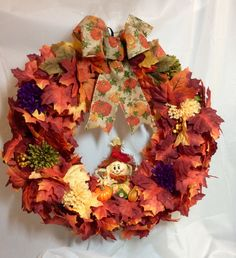 "Fall scarecrow wreath. Orange yellow maple leaves, fall mums on 18"" vine form. Stuffed scarecrow. Pumpkin print bow. Faux flowers, leaves. by KhQualityCreations on Etsy"