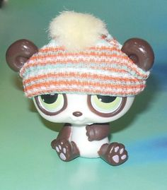 Big eyed LPS toy figurine teddy bear. Head bobbles when touched. Pink toes. Fuzzy pom pom at the top of the hat and is striped. By Hasbro is their Littlest Pet Shop brand dated 2005.