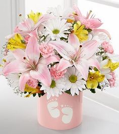 Send wishes of Sweet Dreams to the new baby girl. White daisy poms and pink mini-carnations, yellow alstroemeria and a pink Asiatic lily fill a baby pink ceramic vase. Baby footprints adorn the vase, making it a sweet keepsake for the new parents. Each arrangement is hand-created using the freshest flowers so colors and varieties may vary.  Love it? We deliver nationwide! @veldkamps