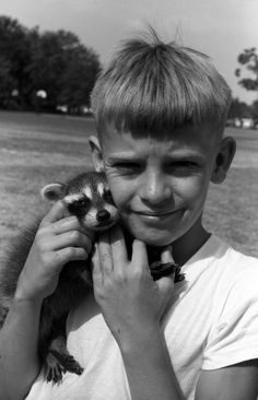 """A little boy with his pet racoon, """"Superman"""" (1966). 