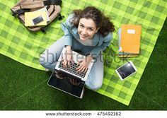 Young smiling student relaxing outdoors, she is sitting on the grass and using a laptop, summer camp concept - Shutterstock Premier