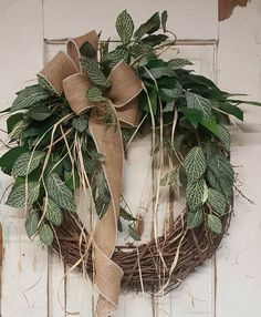 """BEST SELLER This beautiful burlap front door greenery wreath is the perfect simple accent for your door or interior. A wired burlap ribbon makes a simple bow. FRONT DOOR WREATH Average Diameter: 22"""" (tip to tip) This wreath will be created on a grapevine wreath measuring approximately 18"""" Indoor/ Sheltered Outdoor Safe **avoid exposing this wreath to lots of direct sunlight... fading may occur over time :) A wire loop on the back of the wreath for easy hanging from a hook, nail,"""