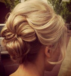 What a pretty and easy up-do for an evening out on the town!! Tease crown of hair and pull into a low pony and tease pony. Leave out face framing curls. Take 1 inch pieces of hair from pony and roll up the pieces into the center of the pony and bobby bin. Continue around the whole pony. Super chic and quick =]